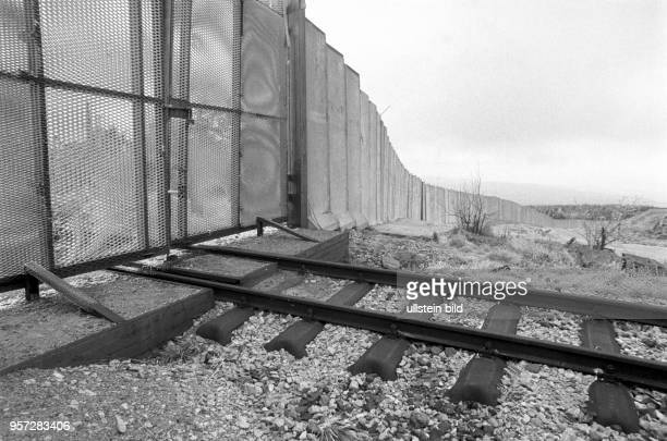 Ein geschlossenes Metalltor in der Grenzmauer am Brocken versperrt die Schiene der Brockenbahn zum Gipfel aufgenommen im Januar 1990 Der Brocken im...
