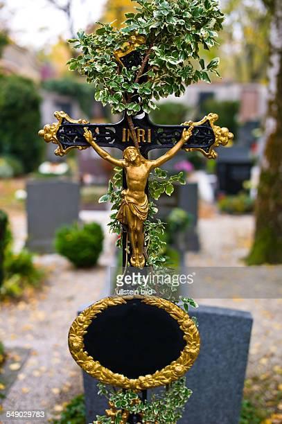 Ein Grabkreuz auf einem Friedhof Mit Efeu überwuchert