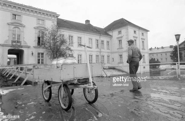 Ein Handkarren mit Milchkannen steht vor dem historische Gebäude Schloss Rheinsberg in Rheiunsberg, Foto vom . Im Schloss ist seit 1953 das...