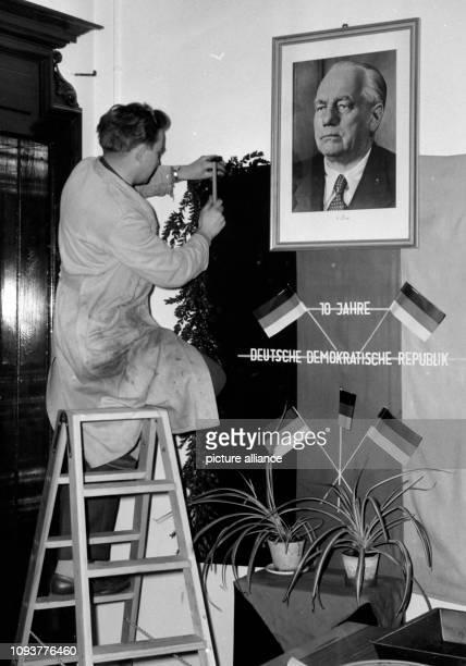 Ein Handwerker schmückt in der Friedrich-Schiller-Universität in Jena in Vorbereitungen zum 10. Jahrestag der DDR eine Wand mit dem Porträt des...