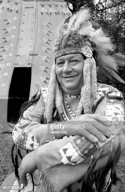 Ein HobbyIndianer der Radebeuler Szene sitzt vor seinem Zelt auf einer Wiese am Elbhang bei Dresden aufgenommen 1988 Alle Kleidungs und Schmuckstücke...
