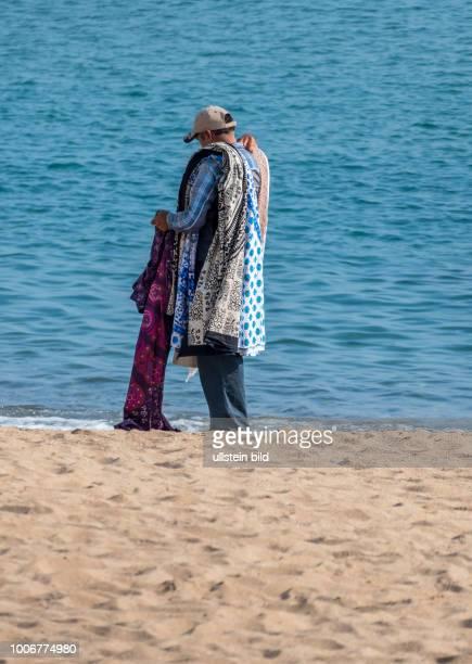 Ein illegaler Verkäufer in Barcelona, Spanien. Preist seine Waren am Badestrand an Touristen an.