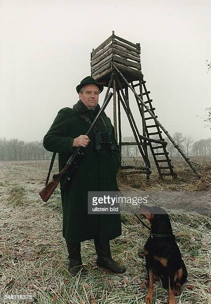 Ein Jäger steht mit geschultertem Gewehr und seinem Jagdhund vor einem Hochsitz - Januar 1996