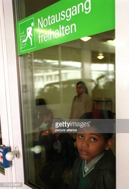Ein jugendlicher Asylbewerber schaut am 14.5.96 durch die Tür der Asylbewerber-Unterkunft auf dem Frankfurter Rhein-Main-Flughafen. Das...