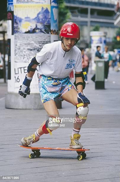 Ein Junge fährt auf dem Gehweg einer Stadt Skateboard. Zum Schutz vor Verletzungen trägt er Helm, Ellenbogenschützer, Handschuhe und Knieschützer....