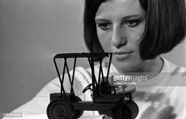 Ein junge Frau zeigt Mode Accessoires der späten 1960er Jahre, Deutschland.