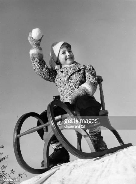 Ein Junge in einer Winterjacke auf einem Schlitten wirft mit einem Schneeball Sonja Georgi Originalaufnahme im Archiv von ullstein bild
