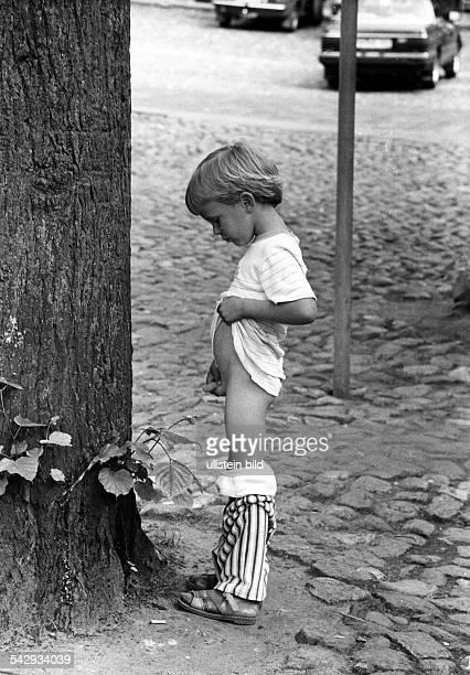 ein Junge pinkelt gegen einen Baum 1985
