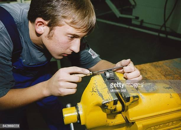 Ein junger Auszubildender arbeitet bei der ZF Getriebe GmbH mit einer Feile an einem Werkstück das er in einen Schraubstock eingespannt hat