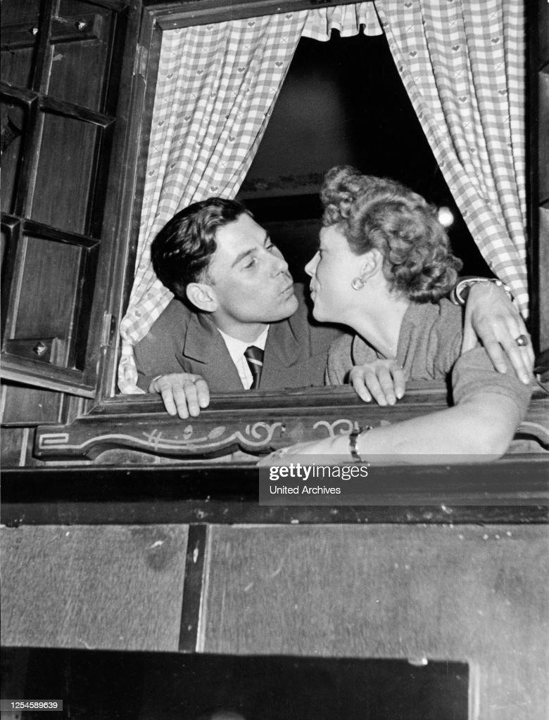 Ein junger Mann und eine junge Frau küssen sich im Fenster