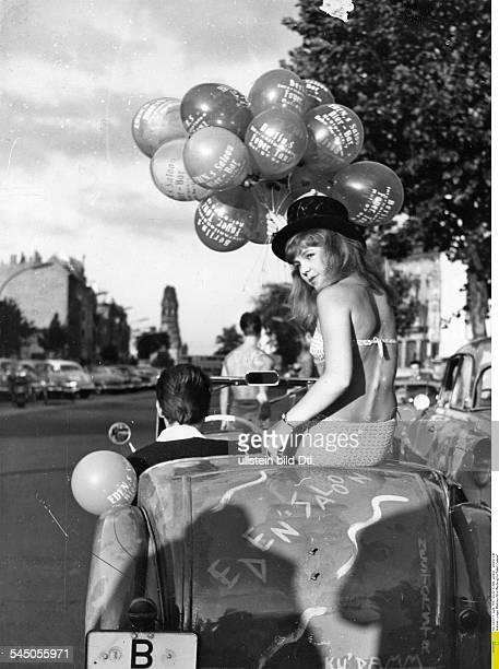 ein junges Mädchen im Bikini hat Luftballons in der Hand uns sitzt in einem Cabriolet das auf dem Kurfürstendamm in Berlin fährt und Werbung für...