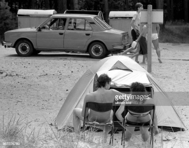 Ein junges Paar in Badebekleidung sitzt vor seinem Zelt auf dem Campingplatz im Ostseebad Prerow auf dem Darß aufgenommen im Sommer 1990 Der...