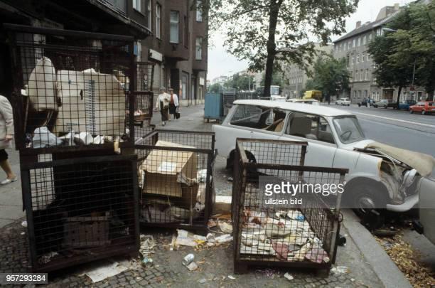 Ein kaputter Pkw Trabant und alte Metallcontainer mit Müll eines Handelsunternehmens stehen auf dem Gehweg der Brunnenstraße in BerlinOst undatiertes...