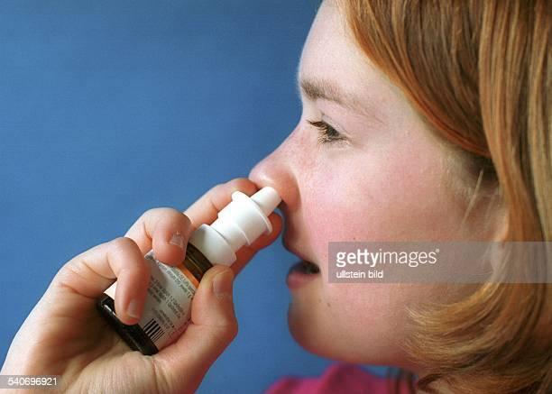 Ein Kind behandelt seinen Schnupfen mit einem Nasenspray Erkältung