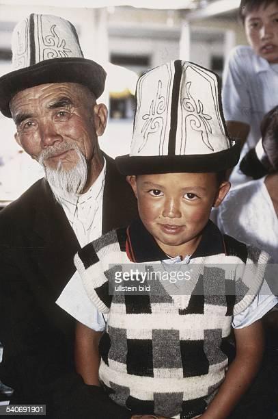 Ein kirgisischer Großvater mit seinem Enkel auf dem Schoß Als Kopfbedeckung tragen beide den traditionellen Kolpak einen hohen weißen Hut mit...