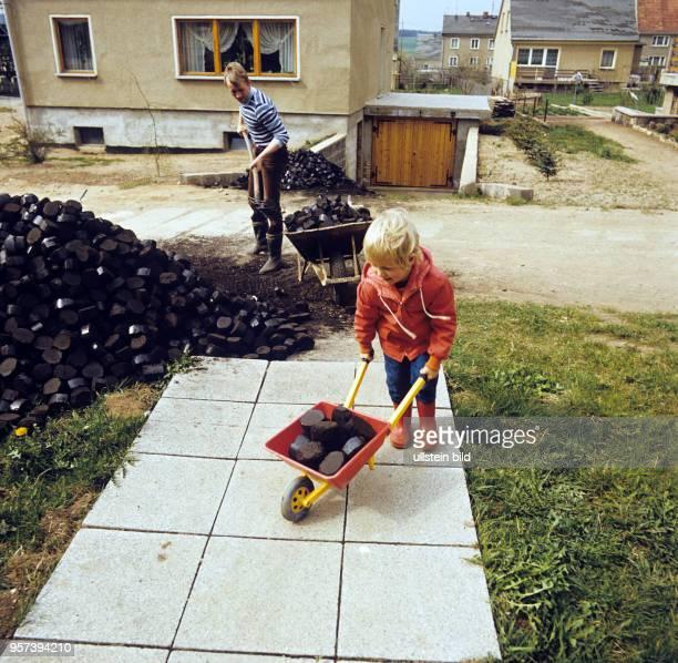 Ein kleiner Junge mit einer Kinderschubkarre hilft beim sogenannten Kohleeinkellern in einer Straße der Gemeinde Frießnitz bei Gera undatiertes Foto...