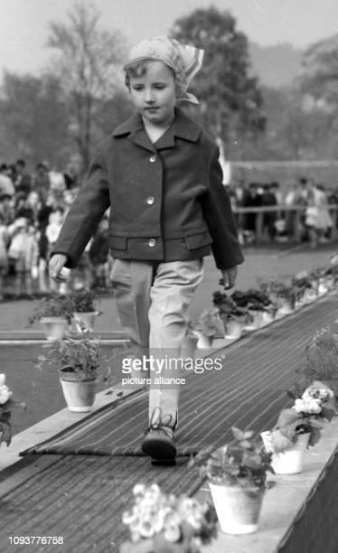 Ein kleines Mädchen zeigt auf einem Laufsteg bei einer Modenschau elegante Kleidung für Kinder eine Kombination von langer Hose Jacke und Kopftuch...
