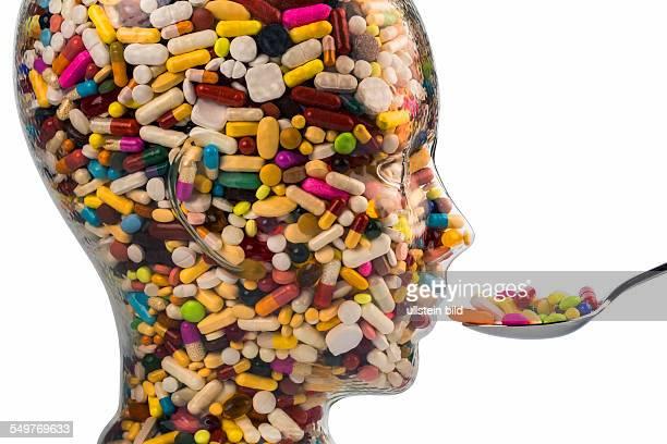 Ein Kopf aus Glas mit vielen Tabletten gefüllt Symbolphoto für Medikamente Mißbrauch und Tablettensucht