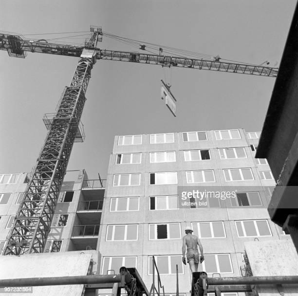 Ein Kran zieht ein Plattenelement zur Montage in das obere Stockwerk an einer Wohnungsbaustelle an der Storkower Straße/Ecke Jakobstraße in Berlin,...