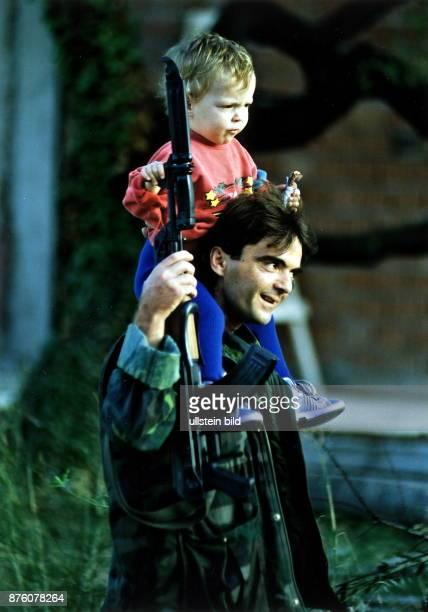 ein kroatischer Soldat mit seiner Kalaschnikow und aufgesetztem Bajonett trägt seine Tochter auf den Schultern November 1991