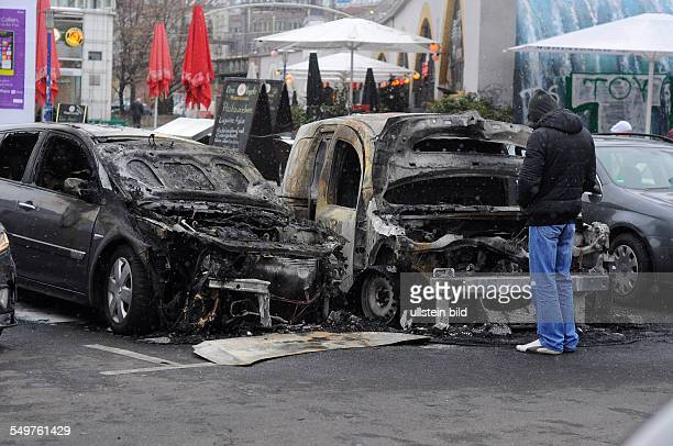 Ein Mann betrachten die ausgebrannten Wracks von zwei Autos in BerlinMitte Sie wurden in der Nacht zuvor von Unbekannten angezündet und durch das...