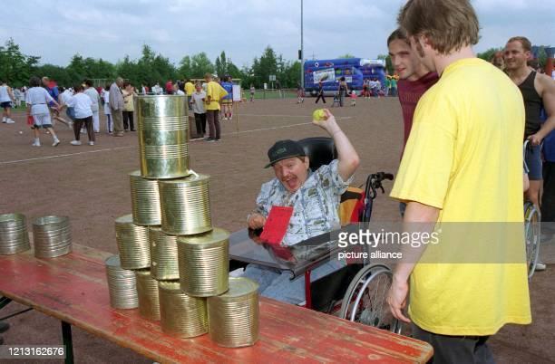Ein Mann im Rollstuhl wirft mit einem Ball nach Blechdosen Mit Spaß und vollem Engagement beteiligen sich am 871999 rund 2500 Kinder Jugendliche und...