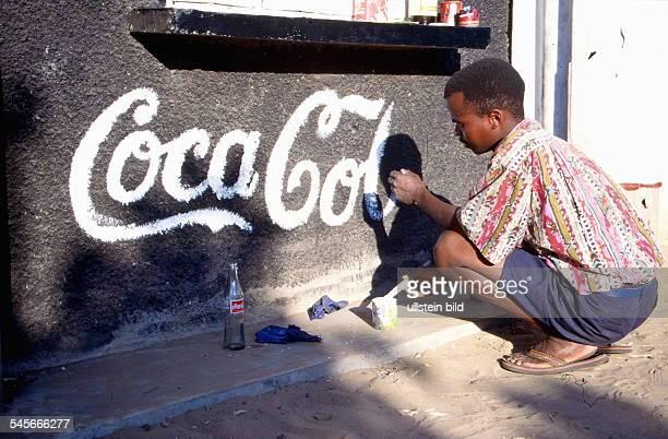 Ein Mann malt den Schriftzug CocaColaauf die Fassade eine Getränkekiosk 1998