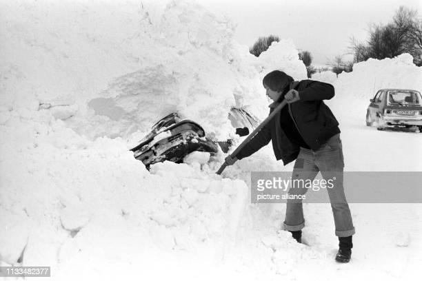 Ein Mann schaufelt sein von Schneemassen bedecktes Auto frei aufgenommen am in Eckernförde Der Temperatursturz vom 29 Dezember 1978 führte in...