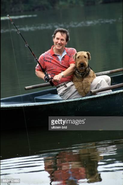 Ein Mann sitzt angelnd im Ruderboot sein Airedale Terrier liegt ihm über den Oberschenkeln