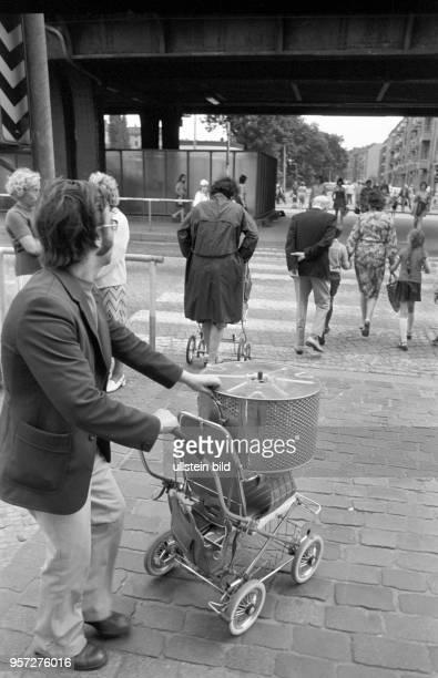 Ein Mann transportiert die neue Trommel für die Waschmaschine per Kinderwagen über die Schönhauser Allee aufgenommen im Juni 1976 im Berliner...