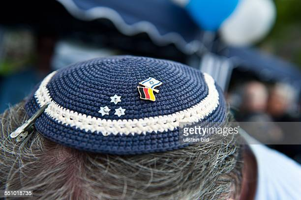 Ein Mann trägt eine besonders schöne Kippa in den Farben seines Landes mit einem Sticker mit DeutschIsraelischer Flagge anlässlich einer Feier des...