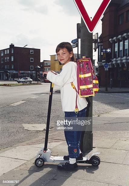 Ein Mädchen mit Schulranzen steht mit seinem Kickboard / Cityroller an einer Straßenkreuzung Aufgenommen um 2000 Symbolbild
