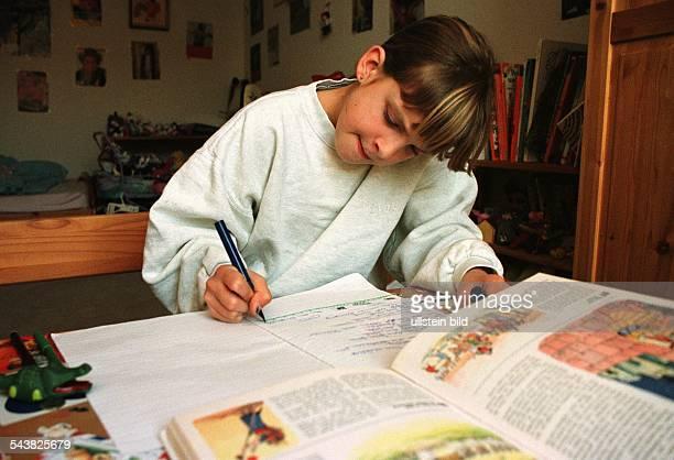 Ein Mädchen sitzt in ihrem Kinderzimmer an einem Schreibtisch vor sich ein aufgeschlagenes bebildertes Buch und schreibt in ein Schulheft Bildung...