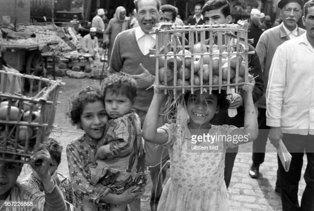 Ein Mädchen trägt einen geflochtenen Korb mit Früchten auf dem Kopf zu einem Verkaufsstand auf einen Basar in Kairo aufgenommen 1972