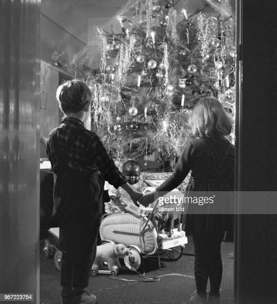 Ein Mädchen und ein Junge Bruder und Schwester halten sich an den Händen und betrachten im Wohnzimmer den geschmückten Weihnachtsbaum und die...
