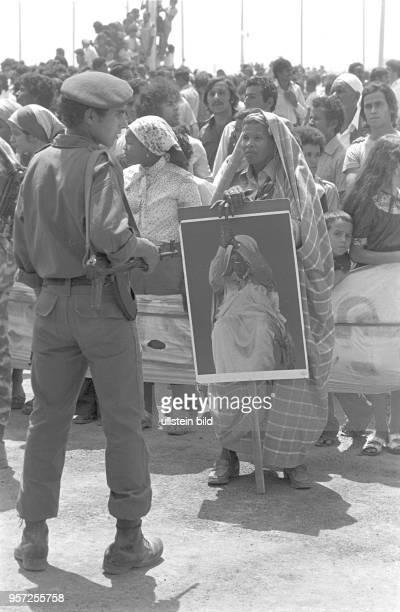 Ein Militär und eine Frau mit dem Bildnis des libyschen Revolutionsführers Gaddafi unter den Zuschauern bei einer Militärparade in Bengasi im...