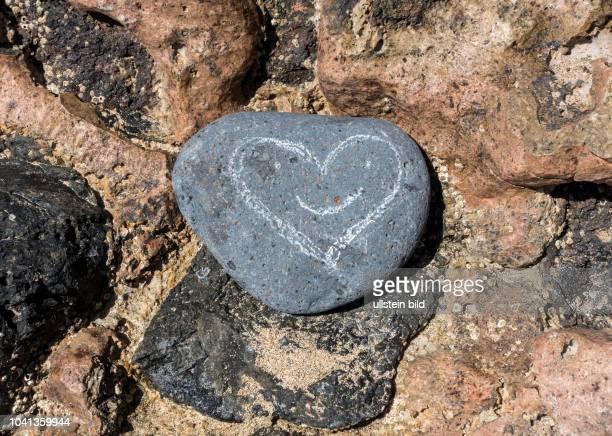 Ein mit einem Herz bemalter Stein in der Naehe von Morro Jable auf der kanarischen Insel Fuerteventura in Spanien.