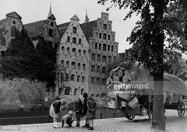 Ein mit Korbwaren beladener Wagen hinter den Salzspeichern, Kinder spielen auf dem Gehwegveröffentlicht: Sieben Tage, 10/1939