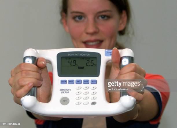 Ein modernes Gerät zum Messen des KörperfettGehalts präsentiert eine junge Frau am 5101999 auf der Internationalen Fachausstellung für Gesundheit und...