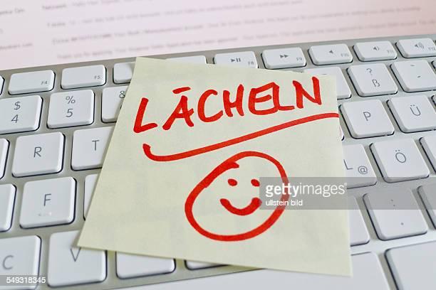 Ein Notizzettel liegt auf der Tastatur eines Computers zur Erinnerung: Lächeln