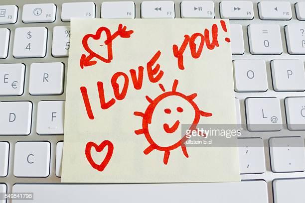 Ein Notizzettel liegt auf der Tastatur eines Computers zur Erinnerung I love you