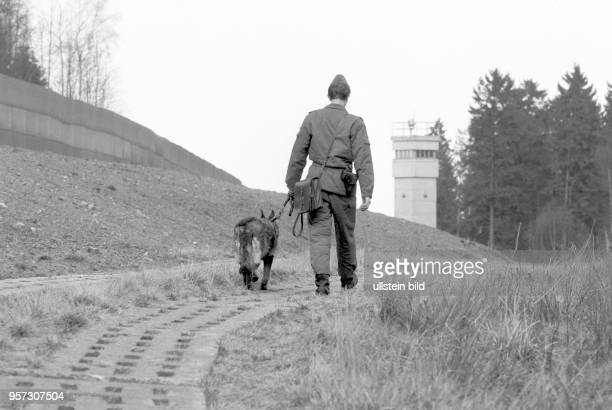 Ein NVAGrenzsoldat mit Hund auf Postengang auf dem Kolonnenweg neben dem Metallgitterzaun der DDRGrenzanlagen im Harz bei Sorge im Grenzgebiet der...