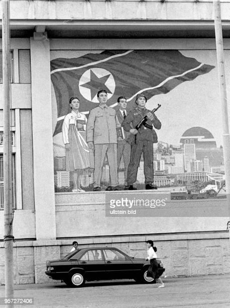Ein Pkw steht unter einem großen Wandgemälde in Pjöngjang der Hauptstadt der Demokratischen Volksrepublik Korea aufgenommen im Juli 1989 während der...