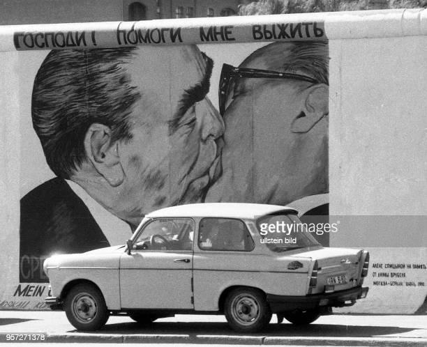 Ein Pkw Trabant steht an der Mühlenstrasse in Ostberlin vor dem Bild Bruderkuss , gemalt vom russischen Maler Dmitri Waldimirowitsch Wrubel ,...