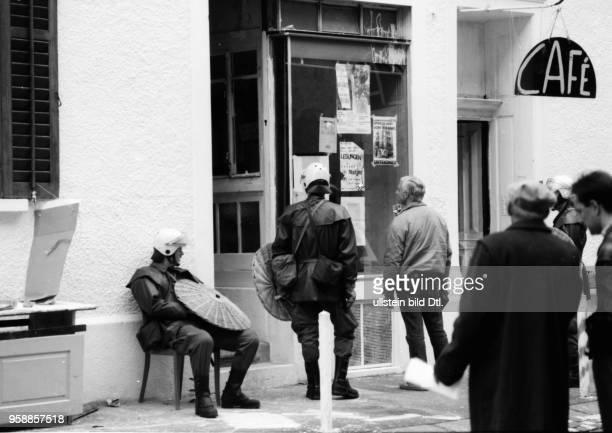 Ein Polizei Grendadier bestückt mit einem Korbschild sitzt auf einem Stuhl vor dem Hauseingang Koechlistrasse 22