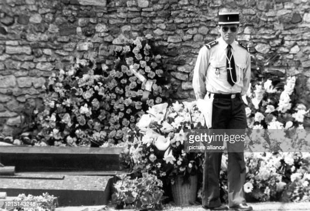 Ein Polizist vor dem blumengeschmückten Grab. Die österreichische Schauspielerin Romy Schneider ist am 2. Juni 1982 auf dem kleinen Dorffriedhof von...