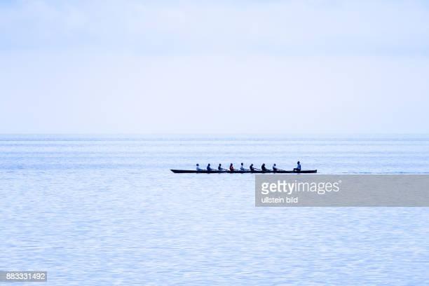 Ein Ruderboot mit acht Ruderern und Steuermann am Meer