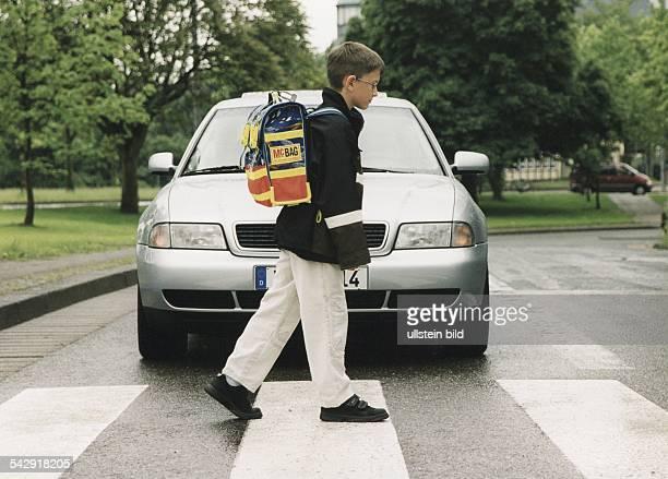 Ein Schüler überquert auf dem Zebrastreifen eine Straße vor einem haltenden Auto. Kind; Kinder. Undatiertes Foto.