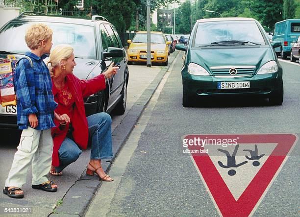 Ein Schulanfänger wird von seiner Mutter am Fahrbahnrand in den Straßenverkehr eingewiesen. Auf der Fahrbahn naht ein PKW heran. Zur Sicherheit der...