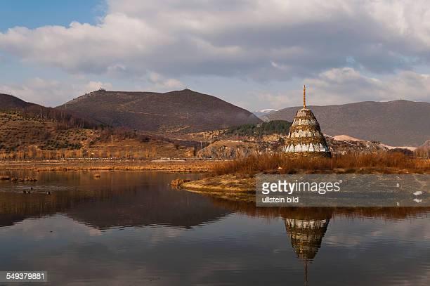 ein See mit Stupa vor dem Kloster Gandem Sumtseling